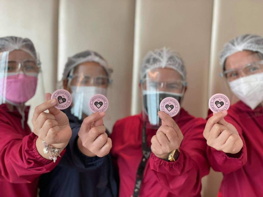 Belo Staff holding i am fully vaccinated pins